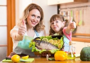 kid daughter and mother show thumb up cooking in kitchen