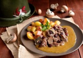 Wild boar meat with roasted potatoes, mushrooms and cranberries